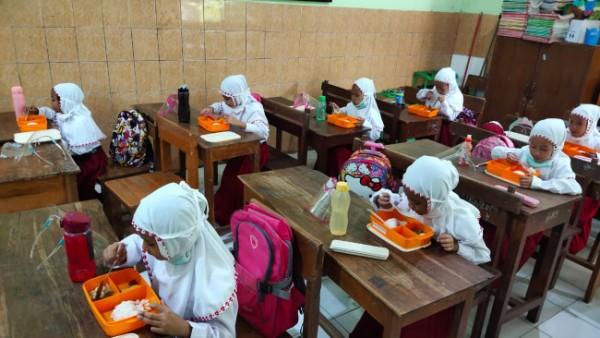 Siswa kelas 1 SDN Kasin yang nampak melakukan kegiatan makan bersama di dalam kelas (Ist)