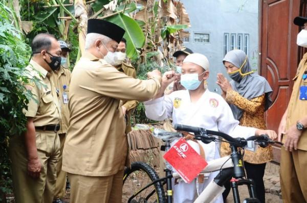 Bupati Malang HM Sanusi (kiri) saat memberikan sepeda angin untuk Aditya Syaiful Anam (foto: Humas Pemkab Malang for MalangTIMES)