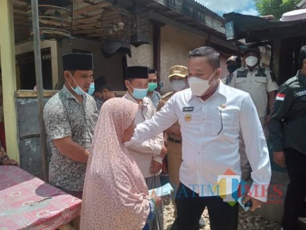 Bupati Sampang H.Slamet Junaidi saat memberikan uang Tunai kepada Rabiyah di desa kembang Jeruk