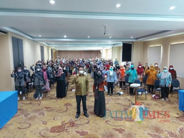 Kepala BPJS Kesehatan Cabang Kabupaten Malang Ariyanti (kanan) bersama anggota Komisi IX DPR RI Ali Ahmad saat berfoto bersama dengan para Kader Pembangunan Manusia, Selasa (14/9/2021). (Foto: Tubagus Achmad/JatimTIMES)