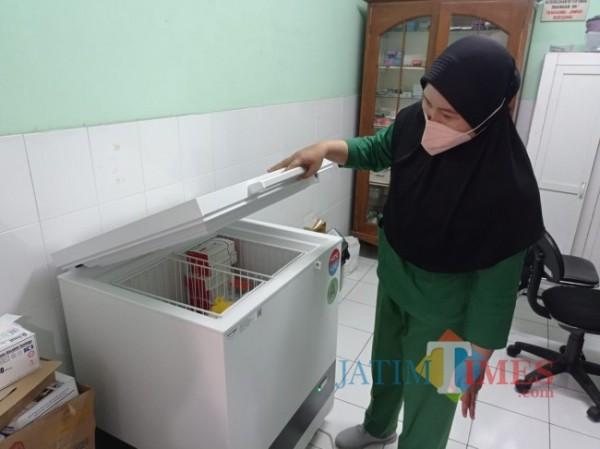 Salah satu petugas Urusan Kesehatan (Urkes) Polresta Malang Kota saat menunjukkan depo storage vial vaksin carrier yang dimiliki oleh Polresta Malang Kota, Rabu (15/9/2021). (Foto: Tubagus Achmad/JatimTIMES)