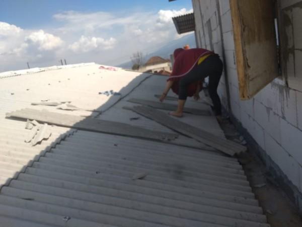 Salah satu warga saat membetulkan atasp rumahnya di Jalan Raya Diponegoro No.37, Dusun Gondang, Desa Tulungrejo, Kecamatan Bumiaji, Kota Batu, Kamis (16/9/2021). (Foto: istimewa)