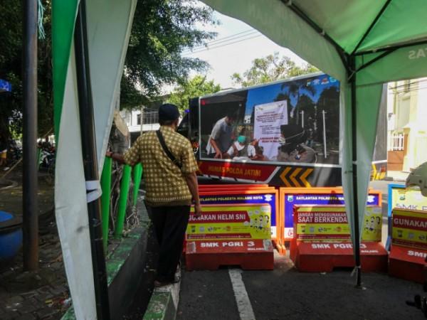 Salah seorang warga yang berada di kawasan Alun-alun Kota Malang tampak menyaksikan tayangan edukasi penerapan protokol kesehatan dan vaksinasi di layar videotron truk milik Polda Jatim, Sabtu (18/9/2021). (Foto: Humas Polresta Malang Kota)