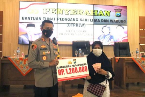 Kapolres Malang AKBP R Bagoes Wibisono saat memberikan bantuan uang tunai sebesar Rp 1,2 juta dari pemerintah untuk pedagang kaki lima dan warung di Kabupaten Malang, Selasa (21/9/2021). (Foto: Humas Polres Malang)
