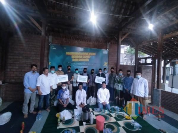 Rumah Sedekah NU bersama Jatim Times, Lazisnu Jatim, dan para donatur memberikan bantuan sebagai bentuk kepedulian kepada para penggali kubur. (Foto: Anggara Sudiongko/MalangTIMES)