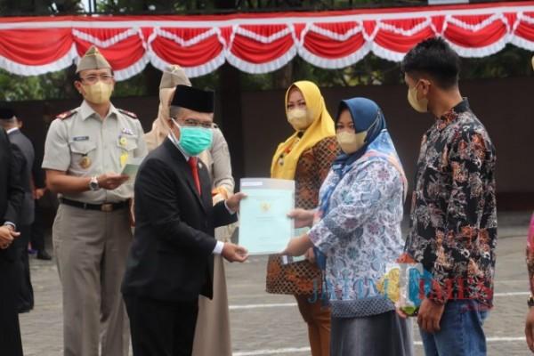 Wakil Wali Kota Batu Punjul Santoso saat menyerahkan sertifikat PTSL kepada salah satu warga Kota Batu, Jumat (24/9/2021). (Foto: Irsya Richa/MalangTIMES)