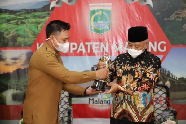 Kepala DP3A Kabupaten Malang Harry Setia Budi saat menyerahkan Penghargaan APE ke Bupati Malang HM. Sanusi.