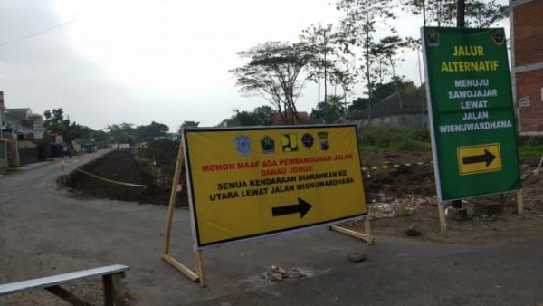 Papan peringatan Jalan Danau Jonge yang tengah dibangun. (Foto: JatimTIMES).