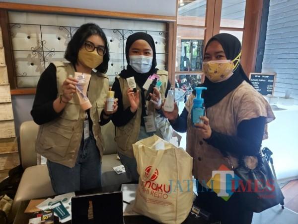 Head Coordinator iLitterless Ence Adinda Dianasta Almas (paling kiri) saat menerima sampah plastik dari salah satu masyarakat Annisa Ramadhani (paling kanan) di Vosco Coffee, Selasa (28/9/2021). (Foto: Tubagus Achmad/JatimTIMES)