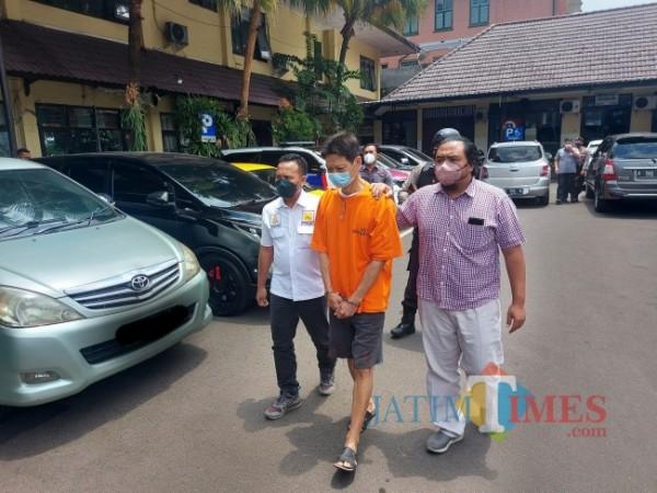 Pelaku berinisial SL yang melakukan pembunuhan berencana terhadap istri sirinya berinisial RDS saat digelandang petugas di Mapolresta Malang Kota, Selasa (28/9/2021). (Foto: Tubagus Achmad/JatimTIMES)