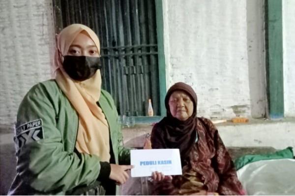 Salah satu karyawan dari Republica Perfumery Malang saat memberikan bantuan terhadap masyarakat yang terdampak pandemi Covid-19. (Foto: Dok. Republica Perfumery Malang)