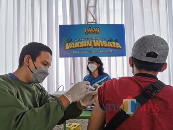 Salah satu tenaga vaksinator saat menyuntikkan Vaksin Covid-19 AstraZeneca terhadap salah satu peserta yang merupakan masyarakat di sekitar kawasan Hawai Group Malang, Rabu (29/9/2021). (Foto: Tubagus Achmad/JatimTIMES)