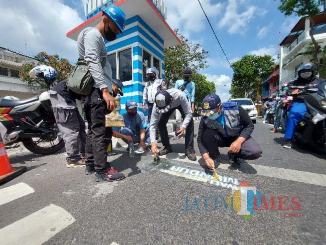 Petugas Dinas Perhubungan Kota Malang saat melakukan pembersihan coretan bernada provokatif.