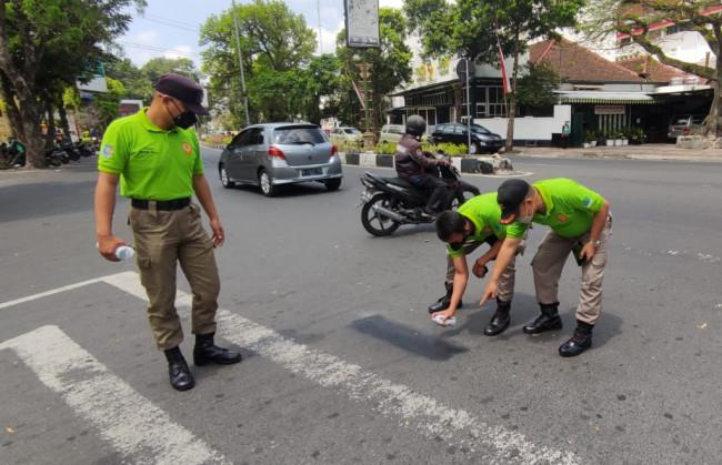 Petugas Satgas Trantibum Satpol PP Kota Malang saat melakukan pembersihan coretan di marka jalan sekitar Monumen Chairil Anwar.