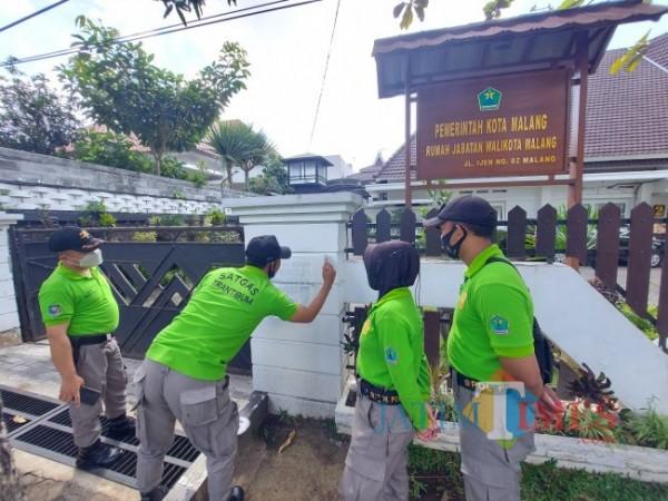 Petugas dari Satgas Trantibum Satpol PP Kota Malang saat melakukan pembersihan coretan vandalisme bernada provokatif di dinding Rumah Dinas Wali Kota Malang, Jalan Ijen Nomor 2, Kota Malang, Jumat (1/10/2021). (Foto: Tubagus Achmad/JatimTIMES)