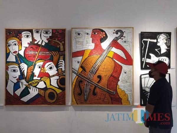 Pengunjung tengah melihat lukisan di pameran Spirit from The East II di gedung Dewan Kesenian Malang. (Foto: Nurlayla Ratri/JatimTIMES)