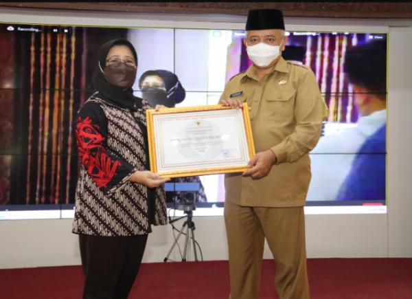 Bupati Malang HM. Sanusi saat menerima Piagam Penghargaan Penerapan Sistem Merit yang diserahkan oleh Komisioner KASN Sri Hadiati.(Foto: Humas dan Prokopim Kabupaten Malang).