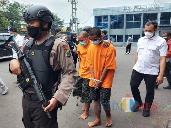 Kedua pelaku saat digelandang petugas untuk meringankan di sel tahanan Mapolresta Malang Kota.