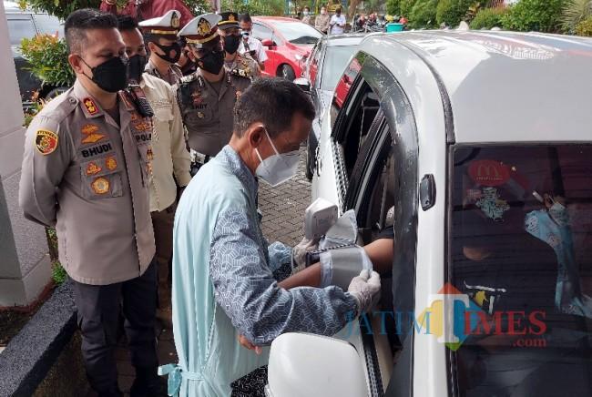 Petugas Dokkes Polresta Malang Kota saat melakukan pengecekan tensi darah calon peserta vaksinasi drive thru.