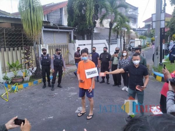 Pelaku pembunuhan istri tengah melakukan reka adegan (Anggara Sudiongko/MalangTIMES)