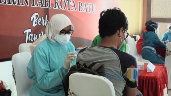 Tenaga kesehatan saat menyuntikkan vaksin Covid-19 di Kota Batu. (Foto: Irsya Richa/ MalangTIMES)