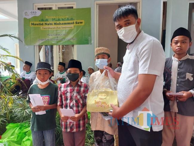 Donatur saat memberikan bantuan kepada anak yatim.