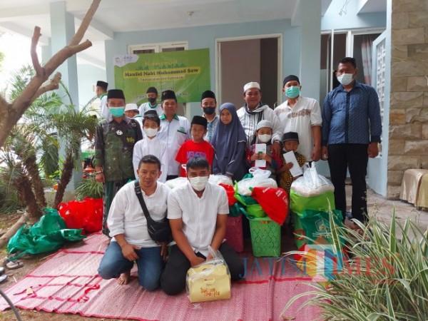 Perwakilan dari anak yatim berfoto bersama dengan para donatur di Rumah Sedekah NU 2 yang berlokasi di Perumahan Bumi Perkasa Regency, Kecamatan Karangploso, Kabupaten Malang, Minggu (10/10/2021). (Foto: Tubagus Achmad/JatimTIMES)