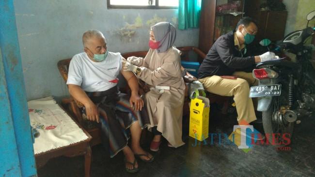 Petugas vaksinator Kecamatan Tajinan didampingi beberapa unsur Muspika saat meakukam vaksinasi door to door.(Foto: Riski Wijaya/MalangTIMES).