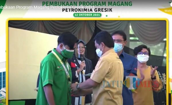 Direktur Keuangan dan Umum Petrokimia Gresik, Budi Wahju Soesilo mengalungkan ID kepada salah satu peserta magang, Rabu (13/10/2021). (Foto : Syaifuddin Anam/GresikTimes)