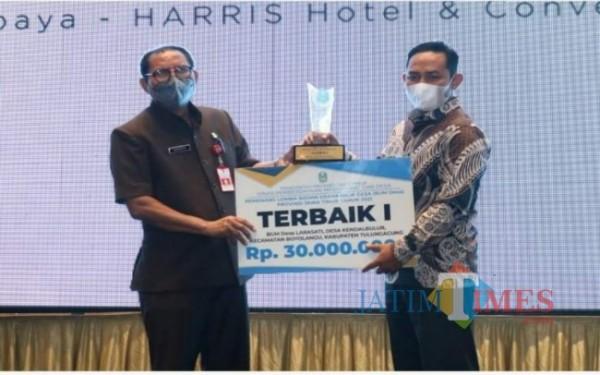 Kades Kendalbulur Anang Mustofa saat menerima penghargaan Terbaik dari Pemprov Jatim atas prestasi BUMDesa Larasati / Foto : Istimewa / Tulungagung TIMES