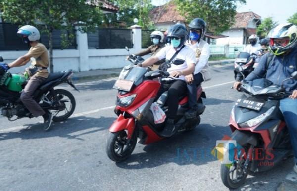 Tampak, Bupati Bangkalan saat dibonceng oleh ajudannya mengelilingi 7 kelurahan di Bangkalan Kota (Foto: Imam/JatimTIMES)